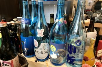 Blue summer shochu bottles line an izakaya counter.